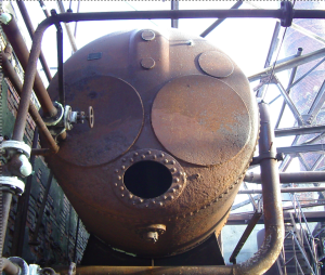 A huge rusty tank, seen from the lower end, looms in an industrial setting of pipes and a smokestack. The end of the tank looks like a face with huge eyes and a black stud-lipped mouth. Definitely scary and looming.