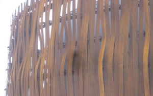 Sculptural wall of rusty bent vertical copper strips.